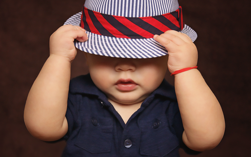 Baby wearing striped hat with hands holding it over eyes