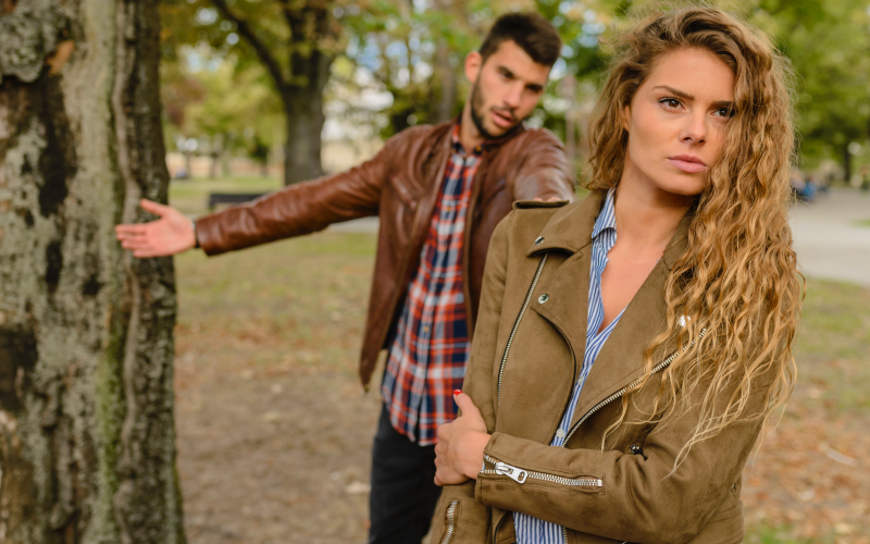 Unhappy woman with back to annoyed man in park