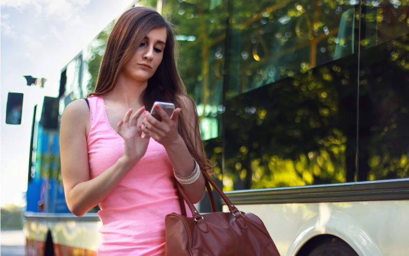 Lone woman by bus looking at mobile